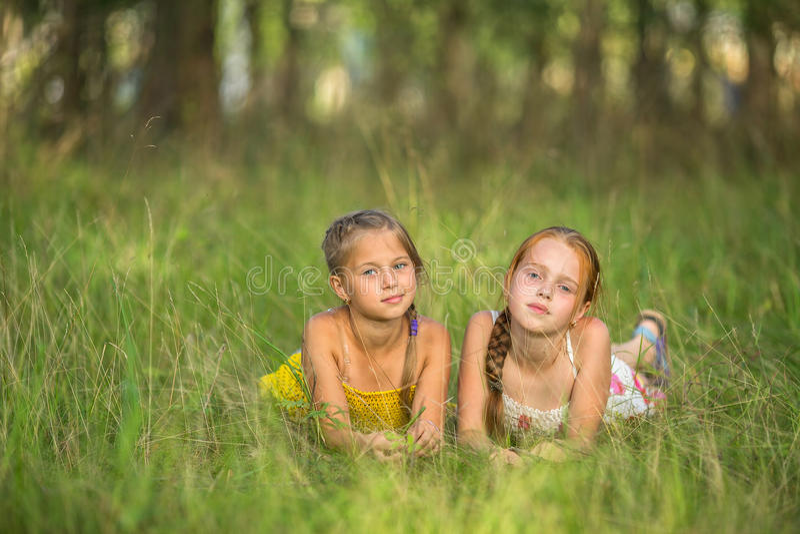 Två lilla systrar som ligger i ängen som ser kameran Natur arkivfoton