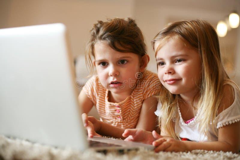 Två lilla systrar som ligger på golvet på vardagsrum och använder l arkivfoton