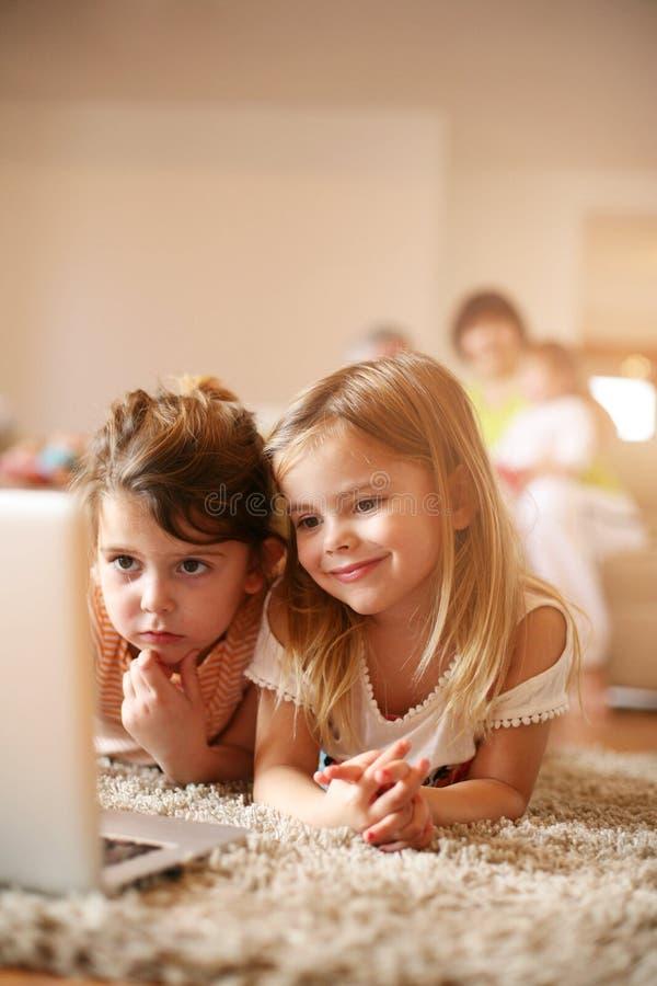 Två lilla systrar som ligger på golvet på vardagsrum och använder l royaltyfri bild