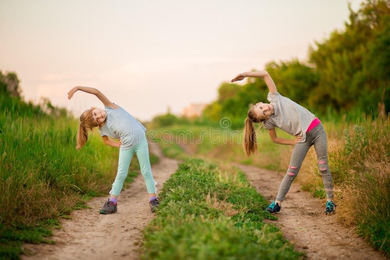 Två lilla systrar som utomhus gör övning Sund livsstil royaltyfria bilder