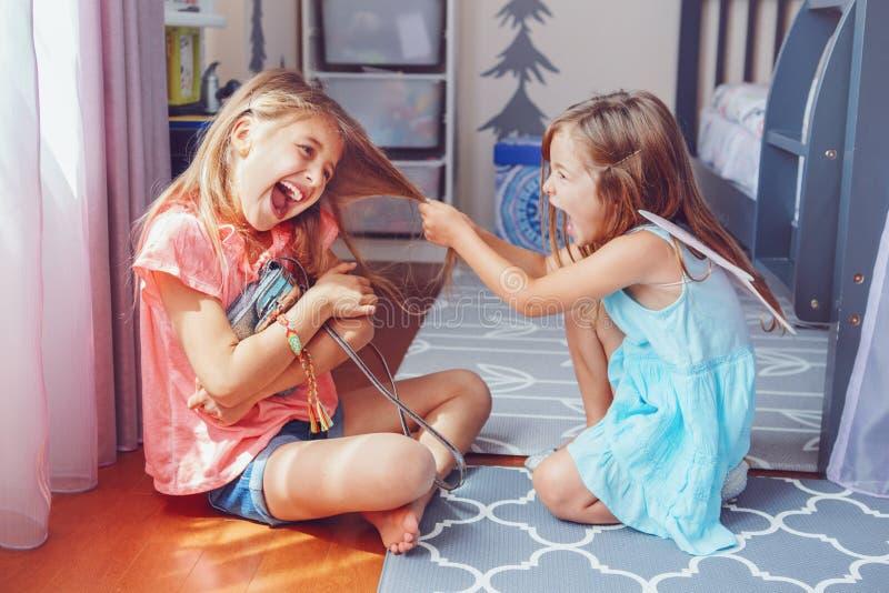 Två lilla tokiga ilskna flickasystrar som har kamp hemma royaltyfri foto