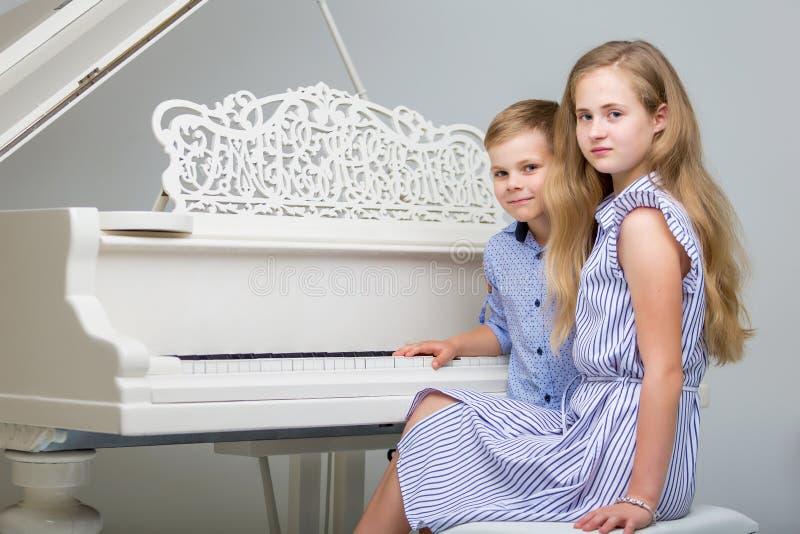 Två lilla ungar flicka och pojke som spelar pianot i vardagsrum eller mus royaltyfri fotografi
