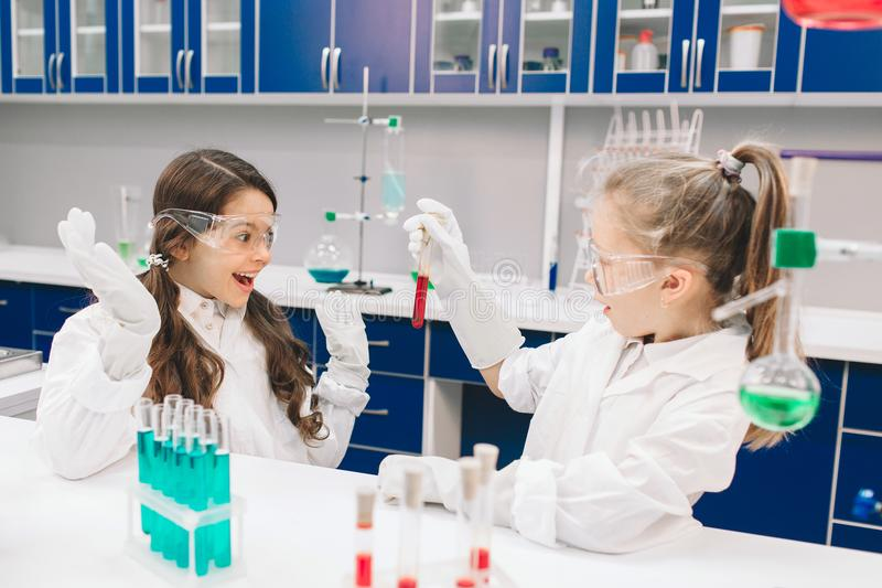 Två lilla ungar i labb täcker att lära kemi i skolalaboratorium Unga forskare i skyddande exponeringsglasframställning royaltyfri bild