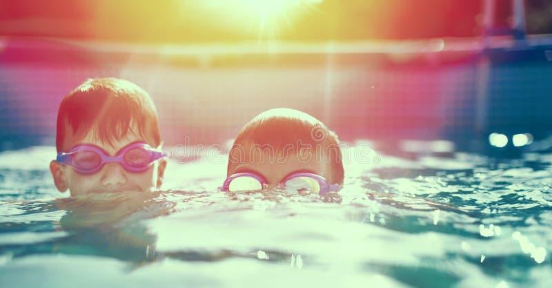 Två lilla ungar i skyddsglasögon som simmar i pöl på solnedgången arkivbilder