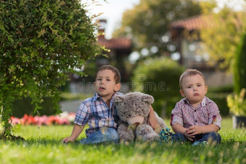 Två lilla ungar som spelar i trädgården royaltyfri bild