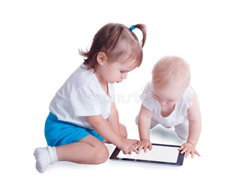 Två lilla ungar som spelar med minnestavladatoren royaltyfria foton