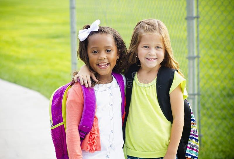 Två lilla ungar som tillsammans går till skolan arkivbilder