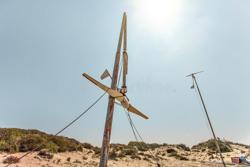 Två lilla vindturbiner, ett av dem som är brutna som står på öken, stark tillbaka ljus sol i bakgrund royaltyfria bilder