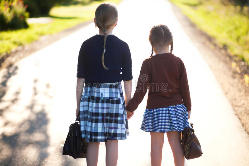 Två liten flickasystrar ordnar till tillbaka till skolan arkivbild