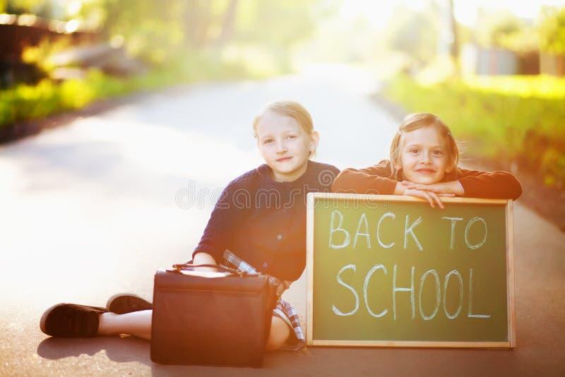 Två liten flickasystrar som väntar på en skolbuss royaltyfri foto