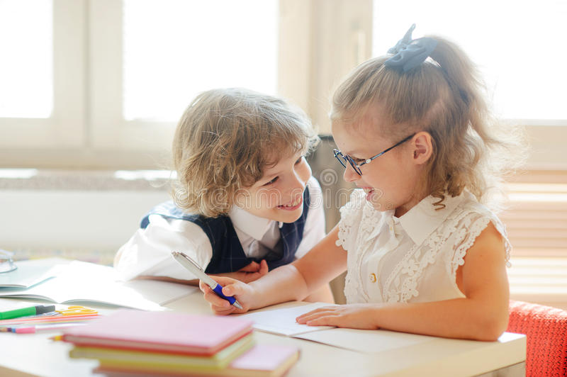 Två liten klasskompis, laddie och girlie, sitter på det samma skrivbordet arkivbilder