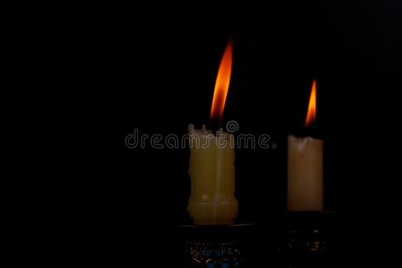 Två ljusa stearinljus som ljust bränner i den svarta bakgrunden arkivbilder