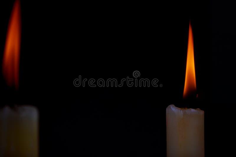 Två ljusa stearinljus som ljust bränner i den svarta bakgrunden arkivbild