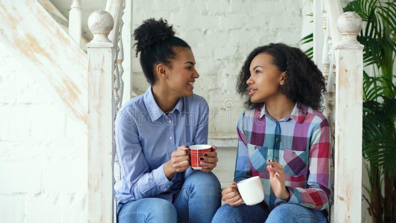 Två lockiga flickasistres för afrikansk amerikan som sitter på trappa, har gyckel som tillsammans skrattar och hemma pratar royaltyfria foton