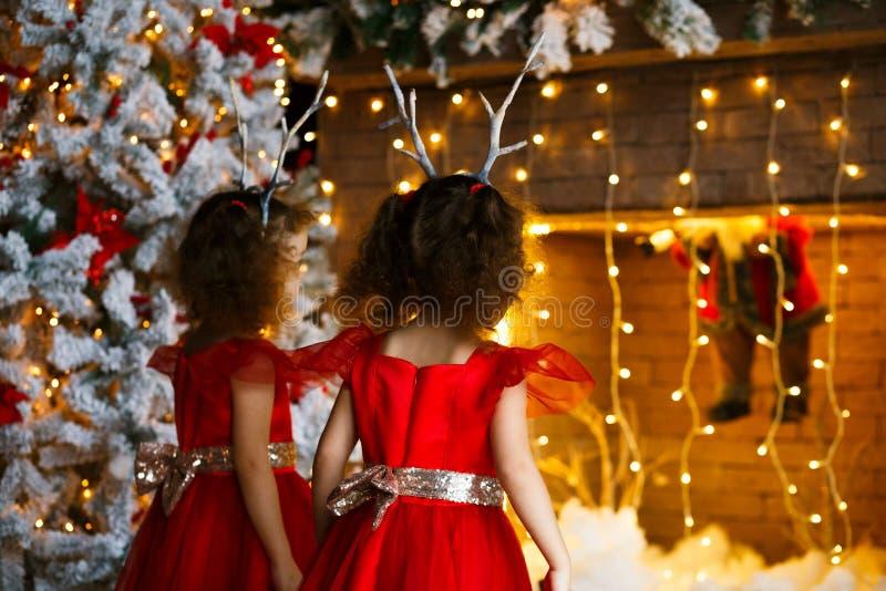 Två lockiga små flickor som ser julspisen nära den härliga julgranen Kopplar samman i röda klänningar som ser fotografering för bildbyråer