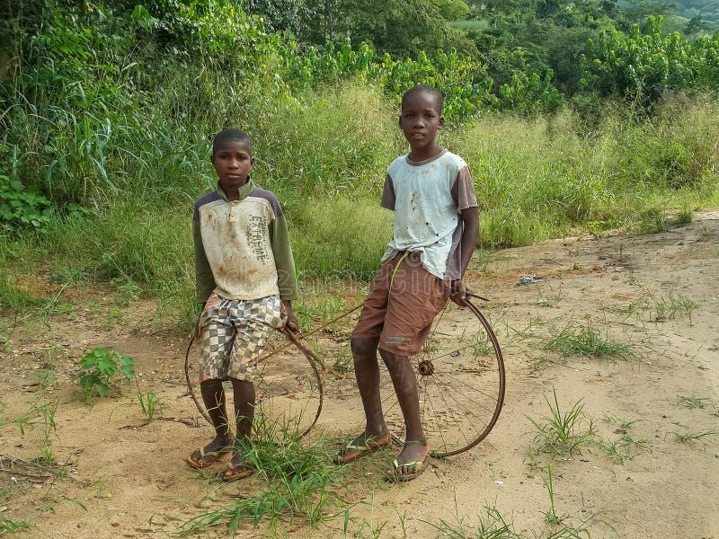 Två lokala afrikanska pojkar som sitter på deras enkla cykelhjul och fotografering för bildbyråer