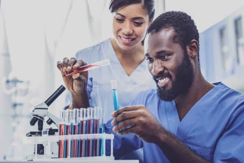 Två lovande kemister som håller ögonen på kemisk reaktion royaltyfria foton