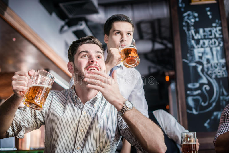 Två lyckade affärsmän dricker öl och jublar och ropar toge royaltyfria foton