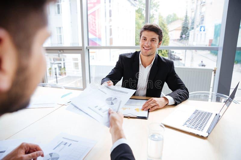 Två lyckade affärsmän som sitter och skapar affärsplan på möte arkivfoton