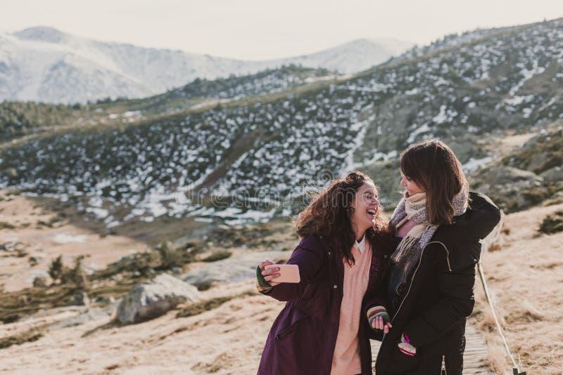 två lyckade fotvandrarekvinnavänner tycker om sikten på bergmaximum Lyckliga fotvandrare i naturen som tar bilder med mobiltelefo royaltyfri fotografi