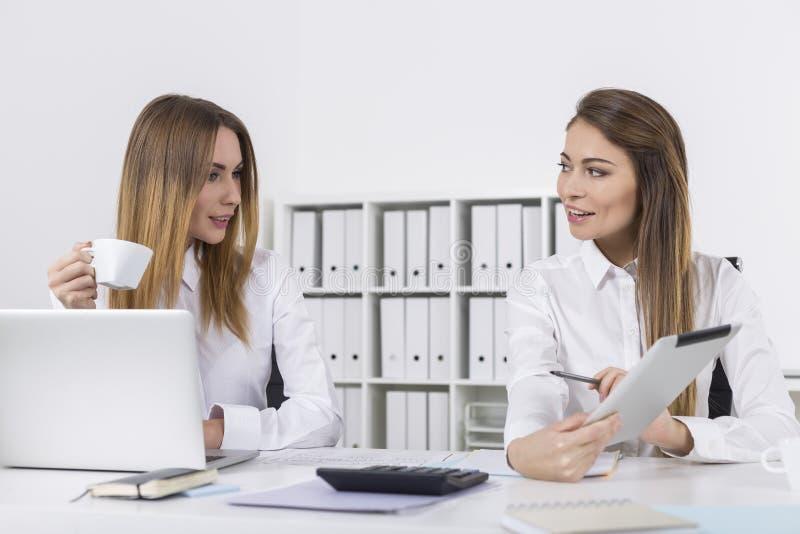 Två lyckliga affärskvinnor i regeringsställning med en minnestavla arkivbild