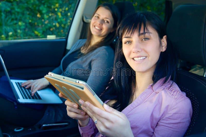 Två lyckliga affärskvinnor som arbetar i bil med teknologi arkivfoton