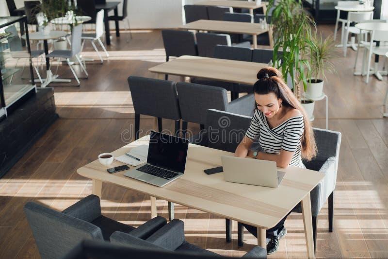 Två lyckliga affärskvinnor som coworking på olika bärbara datorer, men i det samma kafét på den samma tabellen royaltyfria bilder