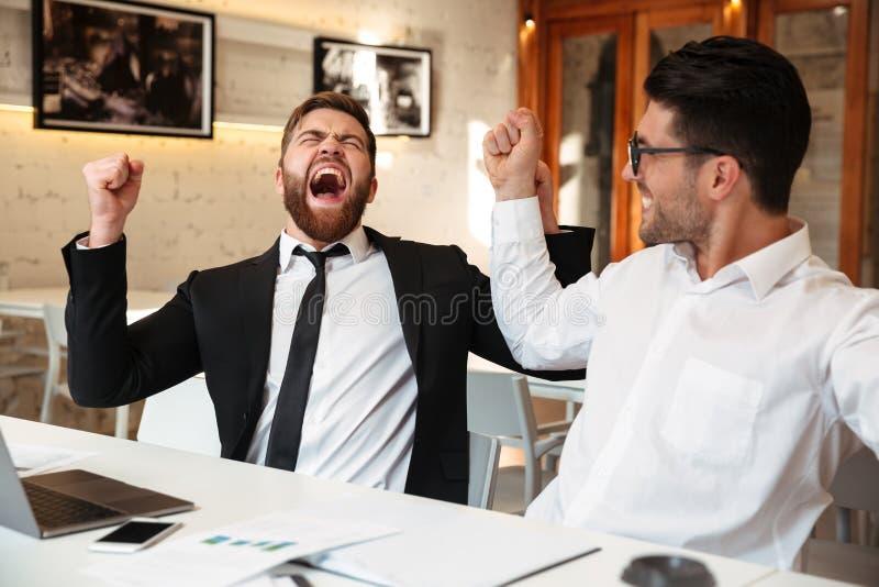 Två lyckliga affärsmän i dräkter som lyfter händer, near bärbara datorn, celebr arkivfoton