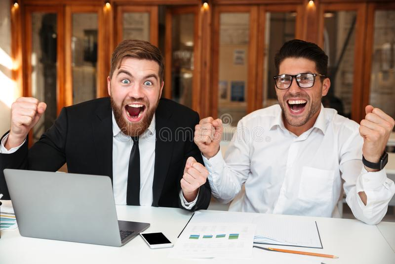 Två lyckliga affärspartners med lyftta händer som ser kameran royaltyfri bild