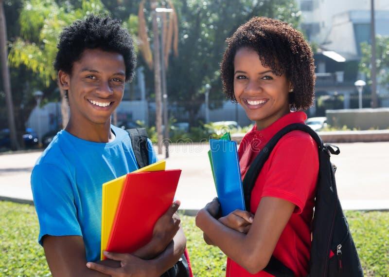 Två lyckliga afrikansk amerikanstudenter på universitetsområde av universitetet fotografering för bildbyråer