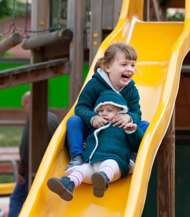 Två lyckliga barn på glidbana royaltyfri foto