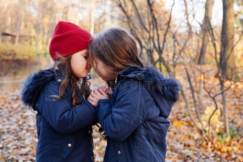 Två lyckliga barn som kramar i höst, parkerar Slut upp den soliga livsstilmodeståenden av två härliga caucasian flickor utomhus,  royaltyfria foton