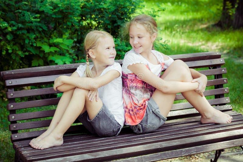 Två lyckliga barn som spelar i parkera på dagtiden arkivbilder