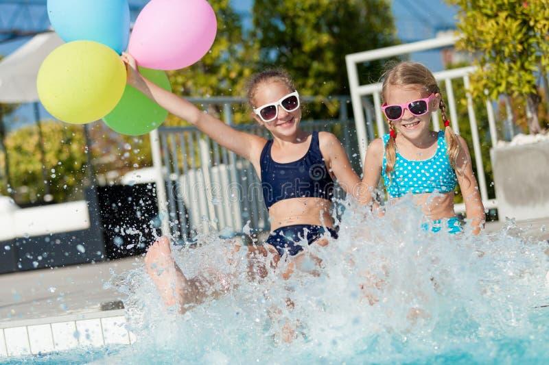 Två lyckliga barn som spelar på simbassängen på dagtiden arkivfoton