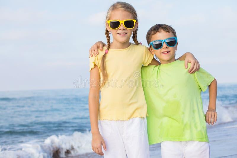 Två lyckliga barn som spelar på stranden på dagtiden royaltyfri foto