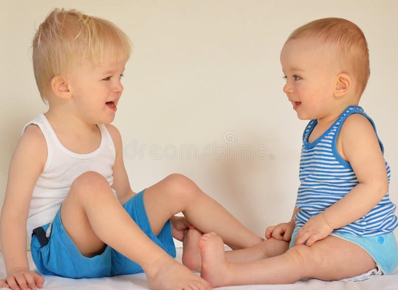 Två lyckliga bröder som sitter och ler på de Barn förälskelsebegrepp royaltyfri bild