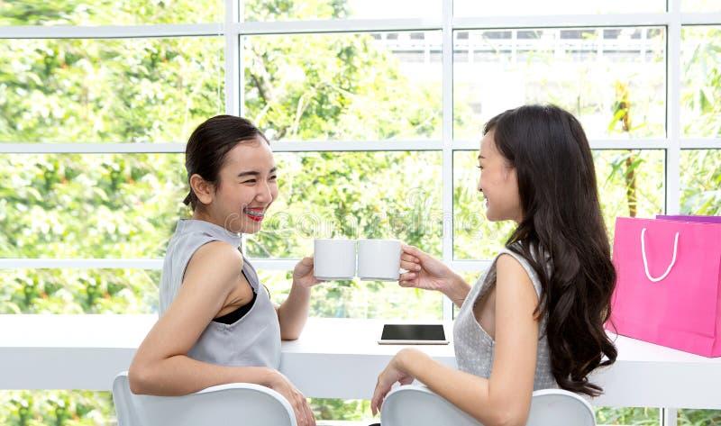 Två lyckliga damkvinnor med kaffekoppen Två bästa unga kvinnor frien royaltyfri bild