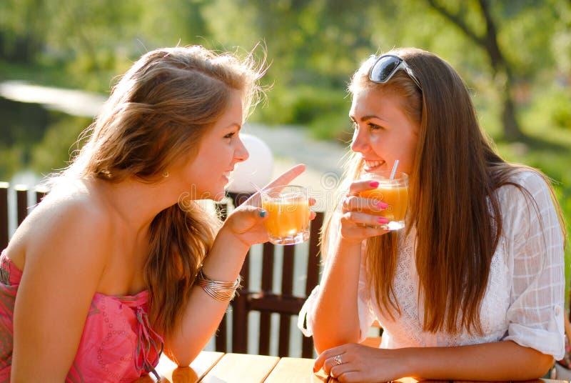 Två lyckliga flickavänner, i cafe & att prata för terrass arkivbild
