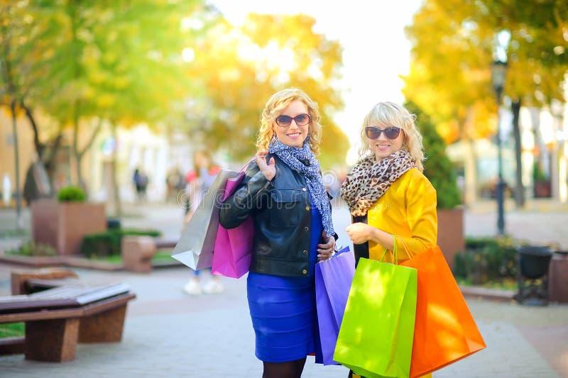Två lyckliga flickor med shoppingpåsar som ler anseende royaltyfri foto