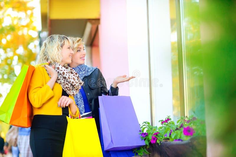 Två lyckliga flickor med shoppingpåsar visar handen royaltyfria foton