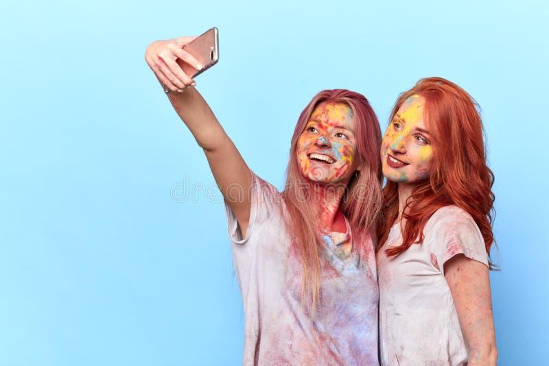 Två lyckliga flickor med smutsig kläder och framsidor som tar en selfie royaltyfria foton