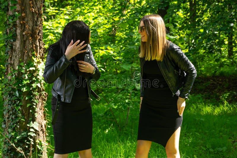 Två lyckliga flickor skrattar med tänder ler på solig dag för vår i skogen royaltyfria foton