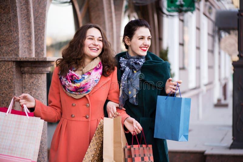 Två lyckliga flickor som går ner gatan, medan shoppa royaltyfria foton