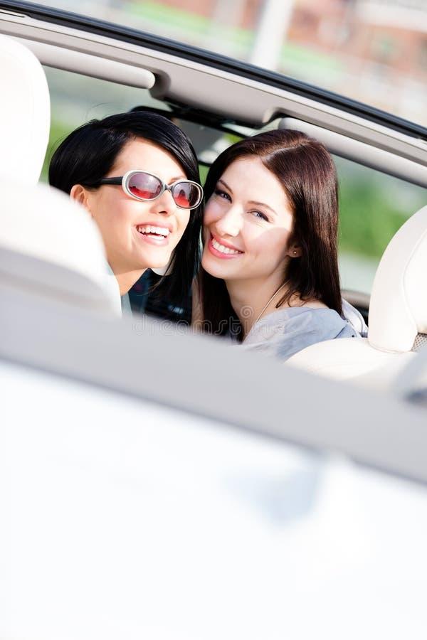 Två lyckliga flickor som sitter i bilen, ser tillbaka royaltyfri bild