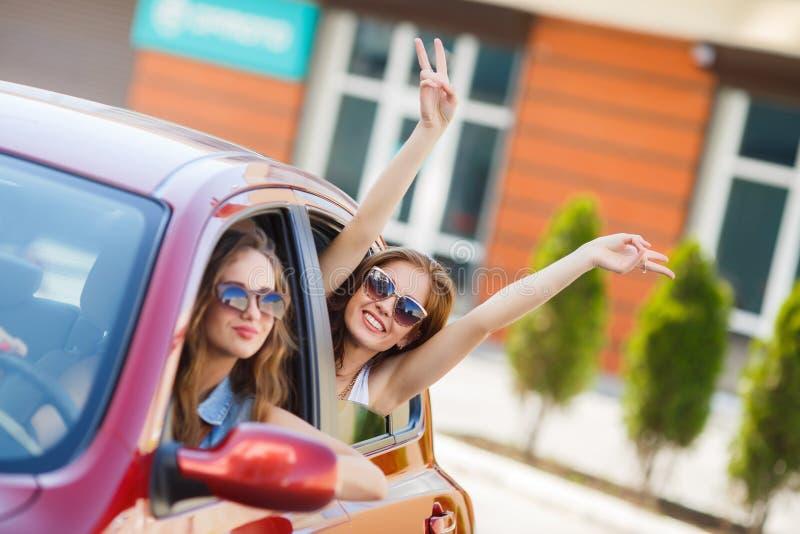 Två lyckliga flickvänner reser i bilen arkivfoton