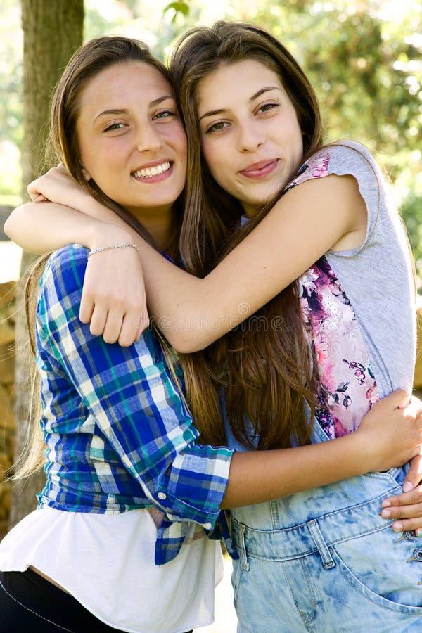 Två lyckliga flickvänner som kramar se kameran parkerar in arkivbild