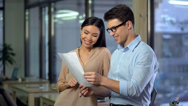 Tv? lyckliga kollegor som l?ser dokumentet, arbete i informell atmosf?r, framg?ng fotografering för bildbyråer
