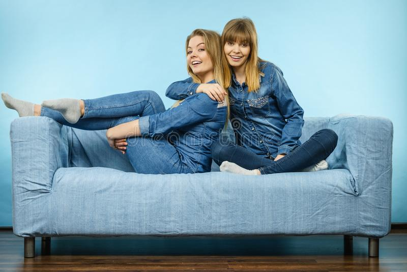 Två lyckliga kvinnavänner som bär jeansdräkten royaltyfri foto