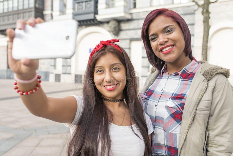 Två lyckliga kvinnavänner som tar en selfie i gatan royaltyfri foto