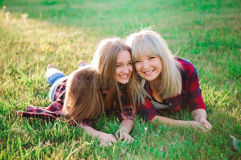 Två lyckliga kvinnliga vänner som spelar och har gyckel i grönt gräs royaltyfri bild